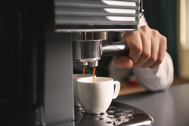 コーヒーメーカーで新鮮なエスプレッソを作る男性のバリスタ、クローズアップ