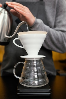 Barista maschio versando acqua nel filtro da caffè