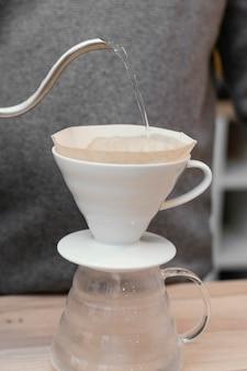 コーヒーフィルターに水を注ぐ男性のバリスタ