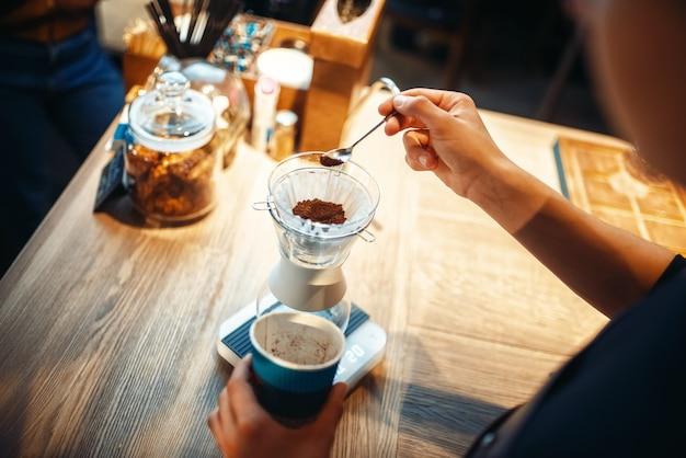 Мужской бариста наливает молотый кофе в стакан
