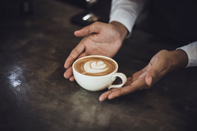 Male barista preparing coffee for customer in coffee shop. cafe owner serving a client at the coffee shop.