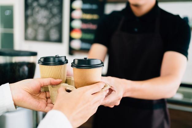 コーヒーショップで持ち帰り用の紙の使い捨てカップでコーヒーを提供する男性のバリスタ。