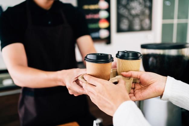 Бариста-мужчина подает кофе в бумажных одноразовых стаканчиках на вынос в кафе.