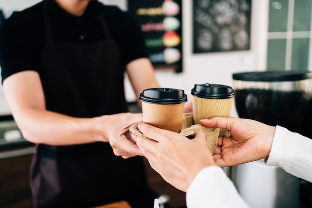 Male barista serving coffee in takeaway paper disposable cups in the coffee shop.