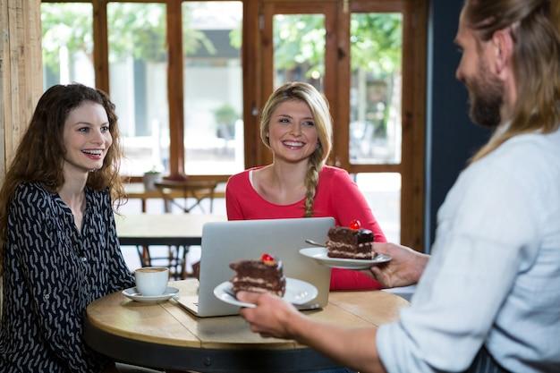 Бариста-мужчина подает десерт клиентам-женщинам в кафе