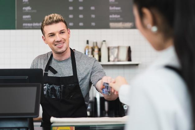 커피 숍에서 유료 커피를 위해 여성 고객으로부터 신용 카드를 복용하는 바 카운터 뒤에 서있는 남성 바리 스타