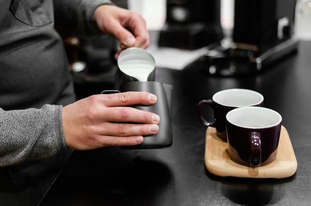 앞치마가 커피 컵을 위해 거품을 낸 우유를 붓는 남성 바리 스타