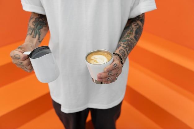 Мужчина-бариста с татуировками подливает молоко в кофе