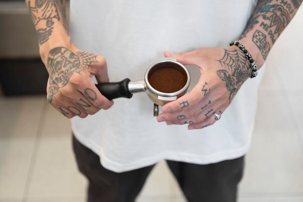 커피 머신용 커피를 준비하는 문신이 있는 남성 바리스타
