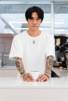 Мужчина-бариста с татуировками, подающий кофе за стойкой
