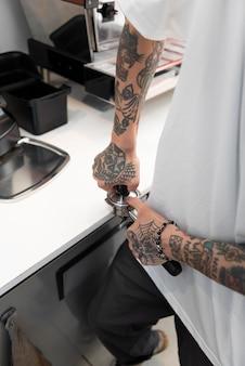 Barista maschio con tatuaggi usando la macchina del caffè al bar