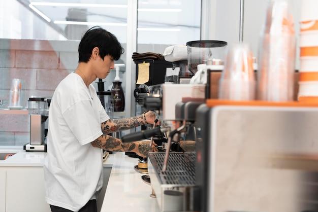 Barista maschio con tatuaggi al lavoro usando la macchina del caffè