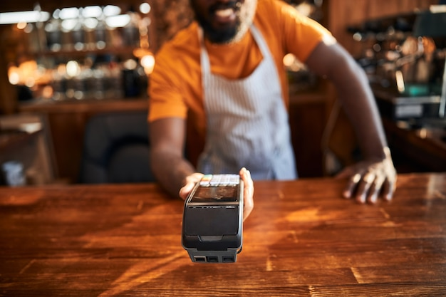 Male barman holding terminal for contactless payment