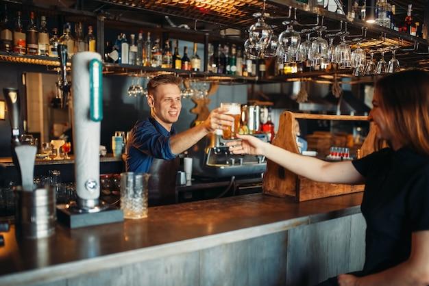 男性バーテンダーがビールのグラスを女性の訪問者に渡します