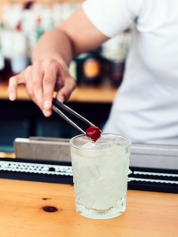 Male bartender adding cherry into drink
