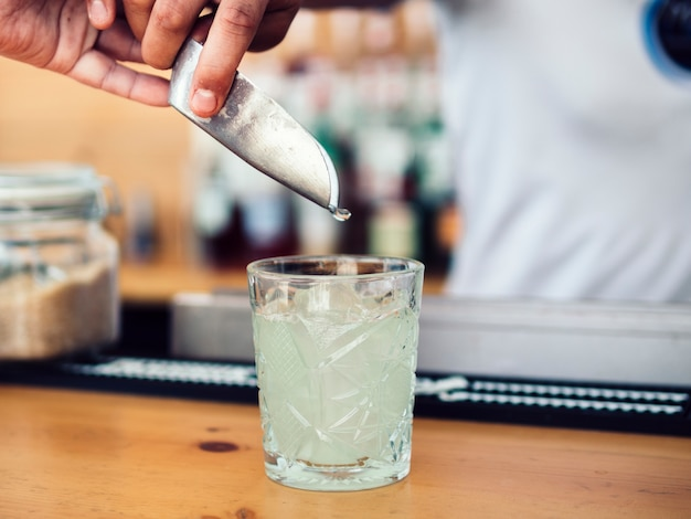 Male bartender adding ice with scoop