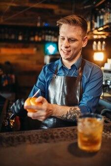 Мужчина-бармен чистит апельсин за барной стойкой