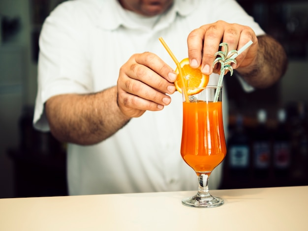 Male bartender decorating exotic cocktail