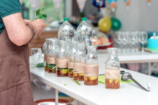 ミントハーブを持って、大きなフレンドリーなパーティーのために夏のさわやかなレモネードドリンクを準備している男性のバーテンダーの手。友人のグループのためのノンアルコールカクテル。