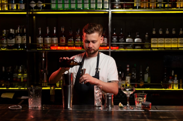 Male bartender making a cocktail with a shaker