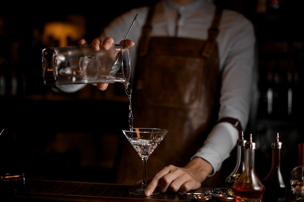 Male bartender pouring an alcoholic drink from the measuring cup to the martini glass