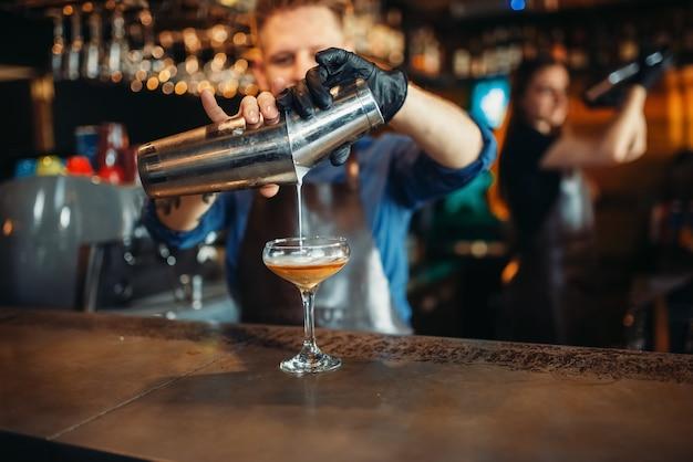 Мужской бармен наливает напиток из шейкера