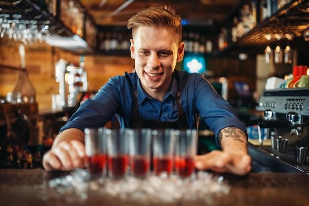 Бармен-мужчина готовит четыре напитка в очках