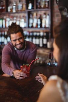 バーのカウンターでお客様にカクテルドリンクを提供する男性バーテンダー