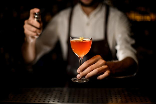 Male bartender serving a cocktail in the glass  spraying on it