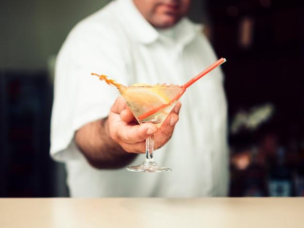 Мужской бармен, где подают коктейль в бокале для мартини