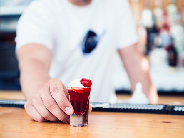Male bartender serving colourful red shot