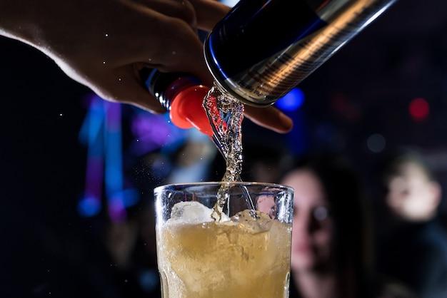 男性バーテンダーがグラスにアルコールカクテルを巧みに注ぐ