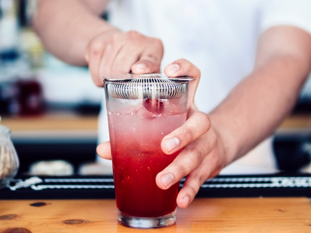 Male bartender using cocktail strainer