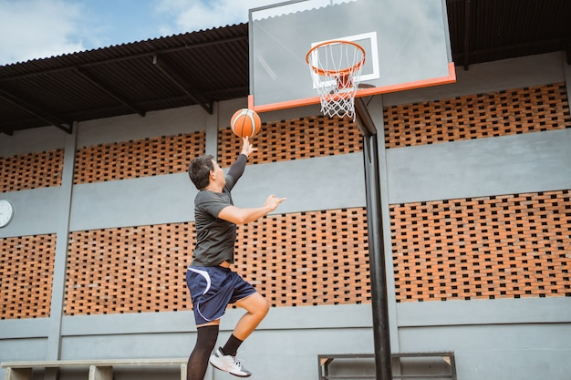 A male basketball player jump shot with the ball