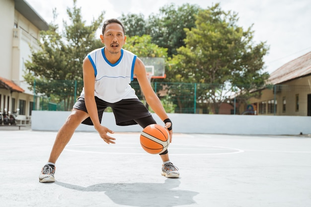 A male basketball player performs a low dribble with the ball while practicing basketball