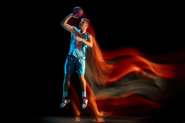 혼합 조명에서 어두운 스튜디오 배경 위에 고립 된 농구를 하는 남자 농구 선수.
