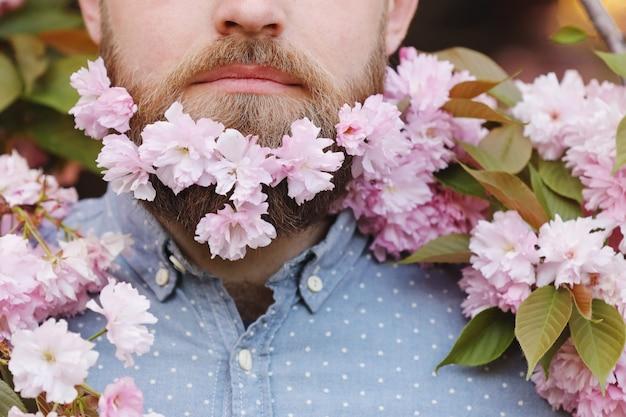 Male beard in sakura flowers. bearded man with cherry flowers in beard, male portrait close-up