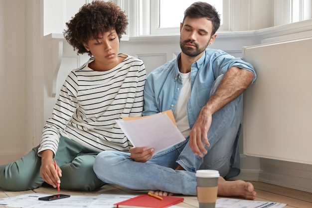 Male bearded accountant and his secretary work together in modern apartment, pose on wooden floor and discuss financial report, have serious gaze in papers, study analytics, feel comfort at home