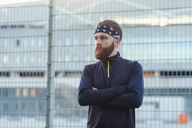 Бородатый спортсмен в спортивной форме и бандане после тяжелых тренировок на детской площадке