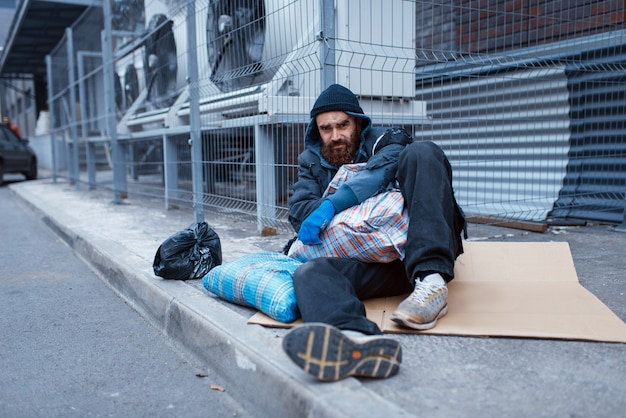 Male bearded beggar lies on city street.