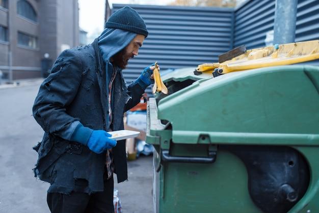 街の通りのゴミ箱で食べ物を探している男性のひげを生やした乞食。
