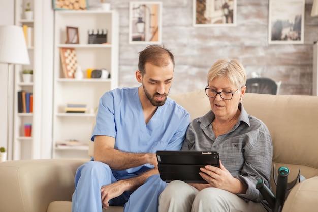 노인 여성이 태블릿 컴퓨터를 사용할 수 있도록 요양원에서 수염을 기른 남성 의사.