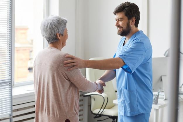 彼は彼のオフィスで彼女に挨拶する年配の女性と手を振って制服を着た男性のひげを生やした医師