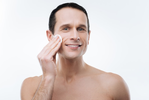 Male beauty. cheerful joyful handsome man smiling and caring about his skin while cleaning it with a cotton pad