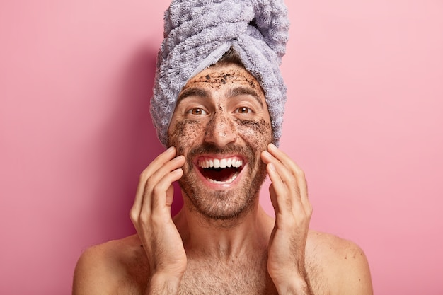 Male beauty concept. happy joyous man applies coffee scrub on face, removes dark dotes, wants to look refreshed, has wrapped towel on head