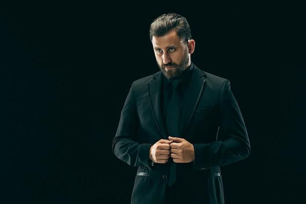 Concetto di bellezza maschile. ritratto di un giovane alla moda con taglio di capelli alla moda indossando abito alla moda in posa su sfondo nero.