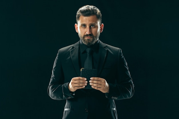 Male beauty concept portrait of a fashionable young man with stylish haircut wearing trendy suit posing over black wall