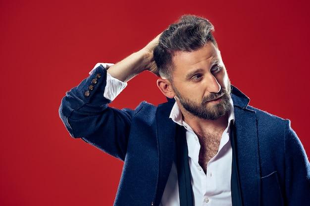 Concetto di bellezza maschile. ritratto di un giovane alla moda con taglio di capelli alla moda che indossa un abito alla moda in posa su sfondo rosso.