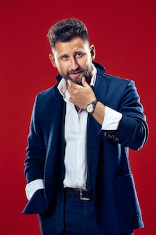 Male beauty concept portrait of a fashionable young man with stylish haircut wearing trendy suit posing over red wall