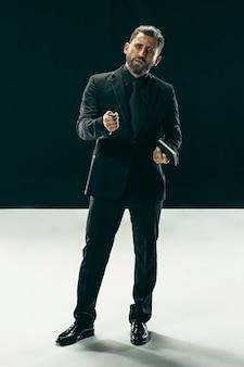 男性の美しさの概念。黒い壁にポーズをとって流行のスーツを着てスタイリッシュなヘアカットを持つファッショナブルな若い男の肖像画。